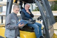 Travailleur sur le matériel et les technologies de construction de camion de transport Photos libres de droits