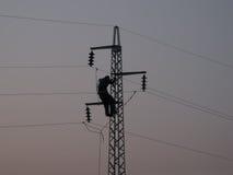 Travailleur sur le pylône de ligne électrique Photographie stock libre de droits