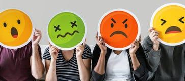 Travailleur tenant des emojis d'expression sur le divan image stock