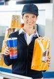 Travailleur tenant le maïs éclaté et la boisson au cinéma photo libre de droits