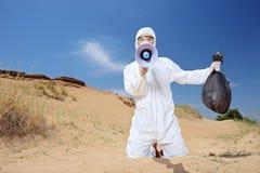 Travailleur tenant un sac et un avertissement de rebut par l'intermédiaire du mégaphone dehors Image libre de droits