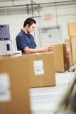 Travailleur vérifiant des marchandises sur la ceinture dans l'entrepôt de distribution Photographie stock