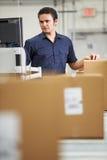 Travailleur vérifiant des marchandises sur la ceinture dans l'entrepôt de distribution Photographie stock libre de droits