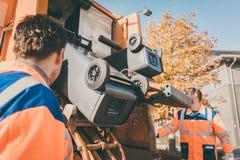 Travailleur vidant la poubelle dans le véhicule de rebut photos libres de droits