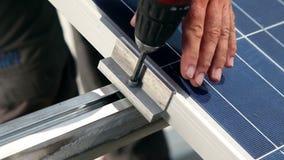 Travailleur vissant sur un modul solaire banque de vidéos