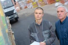Travailleurs à côté de l'empileur de camion transportant des palettes Photo stock