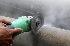 Travailleurs à l'aide de la scie électrique coupant le tuyau Images stock