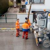 Travailleurs à l'aide du camion de système d'égouts et du grand tuyau travaillant au clogg Photographie stock libre de droits