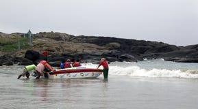 Travailleurs éloignant le bateau de touristes du bord de mer Image libre de droits