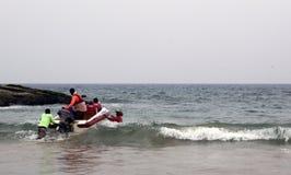 Travailleurs éloignant le bateau de touristes du bord de mer Photographie stock libre de droits