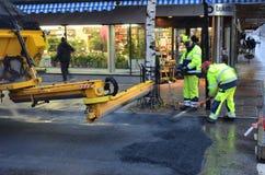 Travailleurs étendant l'asphalte Photographie stock libre de droits