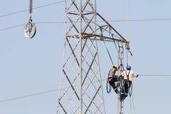 Travailleurs au-dessus d'une tour de tension élevée faisant des réparations Photos libres de droits