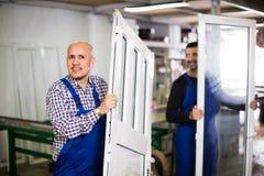 Travailleurs avec des fenêtres et des portes de PVC Photographie stock