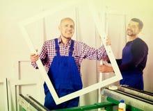 Travailleurs avec des fenêtres et des portes de PVC Photos libres de droits