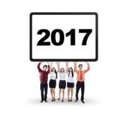 Travailleurs avec le panneau d'affichage et le numéro 2017 Photographie stock libre de droits