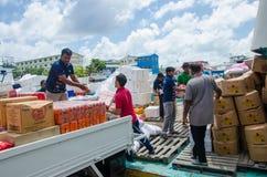 Travailleurs chargeant des marchandises dans le bateau d'approvisionnement Photo libre de droits