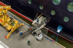 Travailleurs chargeant les faisceaux en acier sur un bateau de croisière Images libres de droits