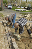 Travailleurs : constructeurs de route étendant des pavés ronds Images libres de droits