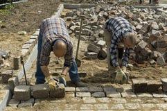 Travailleurs : constructeurs de route étendant des pavés ronds Image libre de droits
