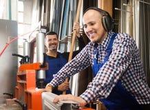 Travailleurs coupant des profils de fenêtre sur le tour d'usine Photographie stock libre de droits