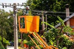 Travailleurs d'électricien coupant les branches que les interferers câblent pour l'électricité photos libres de droits