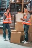 travailleurs d'entrepôt avec les dispositifs numériques photographie stock libre de droits