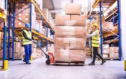 Travailleurs d'entrepôt tirant un camion de palette photo stock