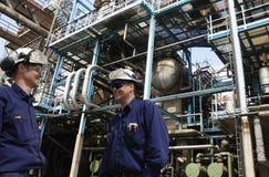 Travailleurs d'huile à l'intérieur de grande raffinerie chimique Photographie stock