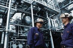 Travailleurs d'huile à l'intérieur de grande raffinerie chimique Image stock