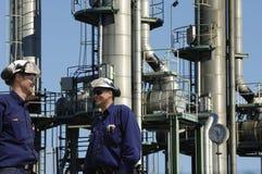 Travailleurs d'huile devant des tours de pétrole et de carburant Photographie stock