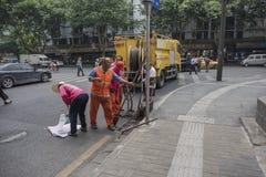 Travailleurs d'hygiène nettoyant des débris d'égout images stock