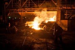 Travailleurs dans l'industrie sidérurgique en versant les scories titaniques liquides du four à arc électrique Images stock