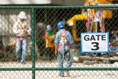 Travailleurs dans le chantier de construction, foyer sur la barrière de maillon de chaîne Images libres de droits