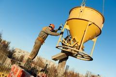 Travailleurs de construction pleuvant à torrents le béton avec le baril Photographie stock libre de droits