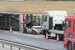Travailleurs de dépanneuse nettoyant l'épave de l'accident de la circulation sur la route, réponse de services des urgences Photographie stock libre de droits
