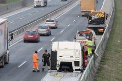 Travailleurs de dépanneuse nettoyant l'épave de l'accident de la circulation sur la route, réponse de services des urgences Image libre de droits
