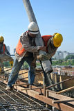 Travailleurs de la construction à l'aide du tuyau concret de la pompe concrète Photo stock