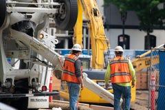 Travailleurs de la construction au site de construction image stock