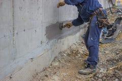 Travailleurs de la construction avec l'isolation hydraulique appliquée de brosse photographie stock libre de droits