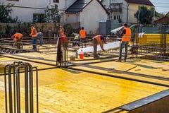 Travailleurs de la construction avec les gilets réfléchissants fabriquant le rei en acier photo stock