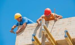 Travailleurs de la construction clouant le coffrage en place Photographie stock