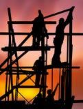 Travailleurs de la construction contre le coucher du soleil coloré Image libre de droits