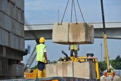 Travailleurs de la construction empilant le bloc d'essai de charge de maintien au chantier de construction Images stock