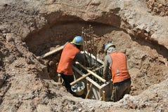 Travailleurs de la construction employant la broyeur pour couper l'acier Photographie stock