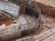 Travailleurs de la construction fabriquant la barre en acier de renfort ? l'int?rieur du coffrage de bois de construction au chan photos libres de droits