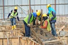 Travailleurs de la construction fabriquant la barre de renfort de faisceau au sol Photographie stock libre de droits