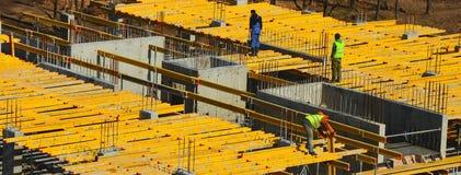Travailleurs de la construction installant montant le coffrage horizontal dessus image stock