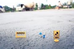 Travailleurs de la construction (miniatures) sur le plancher en béton Photos libres de droits