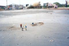 Travailleurs de la construction (miniatures) sur le plancher en béton Photo stock