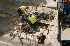 Travailleurs de la construction réparant un tube cassé images libres de droits
